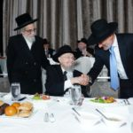 Rabbi Dovid Feinstein being greeted by Shmuel Yosef Reider