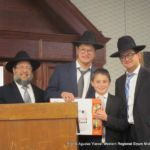 Rabbi Levi, Mordechai Joseph and Shmuel Kagan with a prize winner.