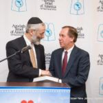 Rabbi Zwiebel, presenting Speaker Coughlin with an inscribed biography of Rabbi Moshe Sherer, zl, longtime president of Agudath Israel of America